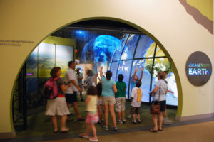 People standing in front of a museum exhibit with a large map of Earth.