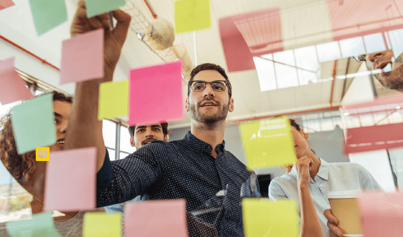 Photo of professionals collaborating around a wall of post-its
