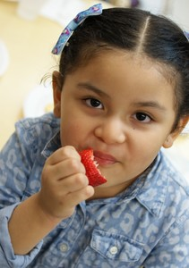 Young girl with a piece of fresh fruit.
