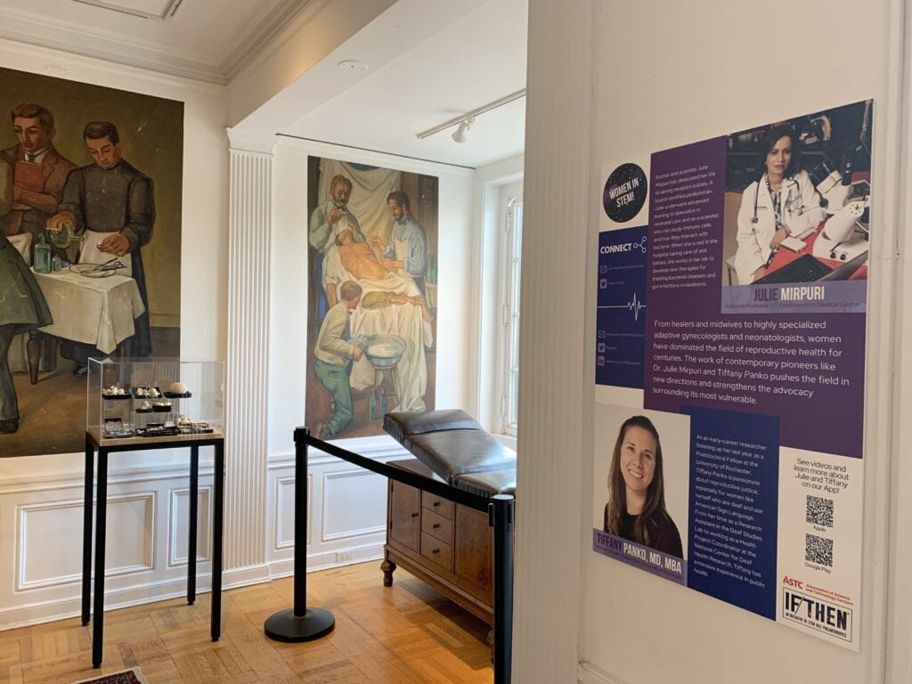 A museum exhibit featuring artwork, an old operating table, and a colorful wall display featuring women in science careers.